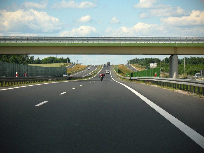 spacerowicze skracają sobie drogę przez autostradę